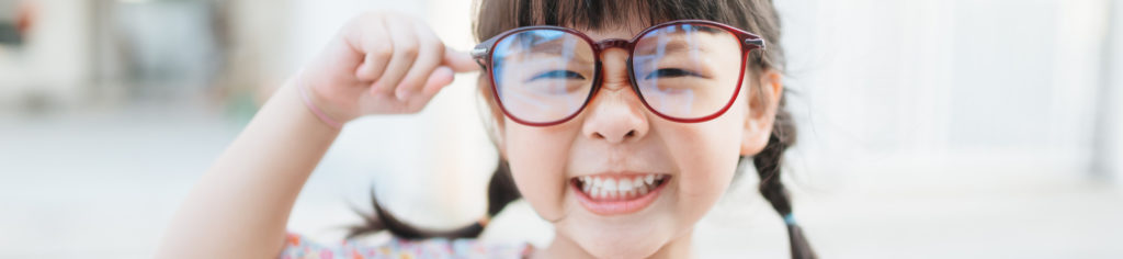 Little nearsighted girl wearing big glasses and smiling