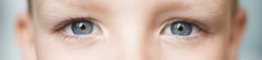 Close-up of a blue-eyed child with myopia