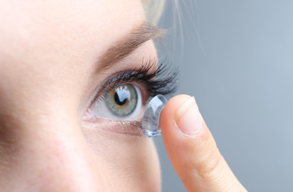 Young lady with green eyes putting contact lens into her left eye.