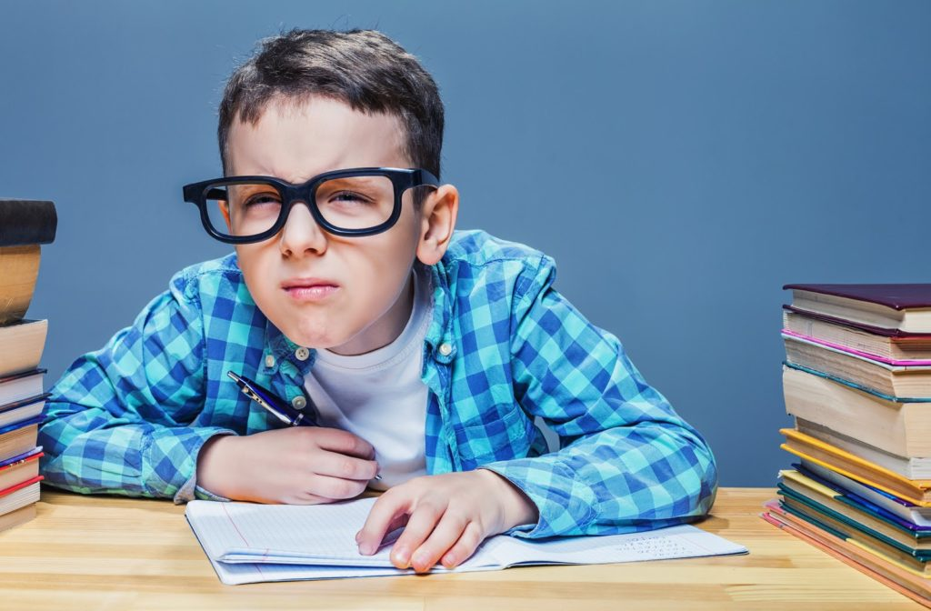 Boy with glasses squinting to better see due to blurry vision