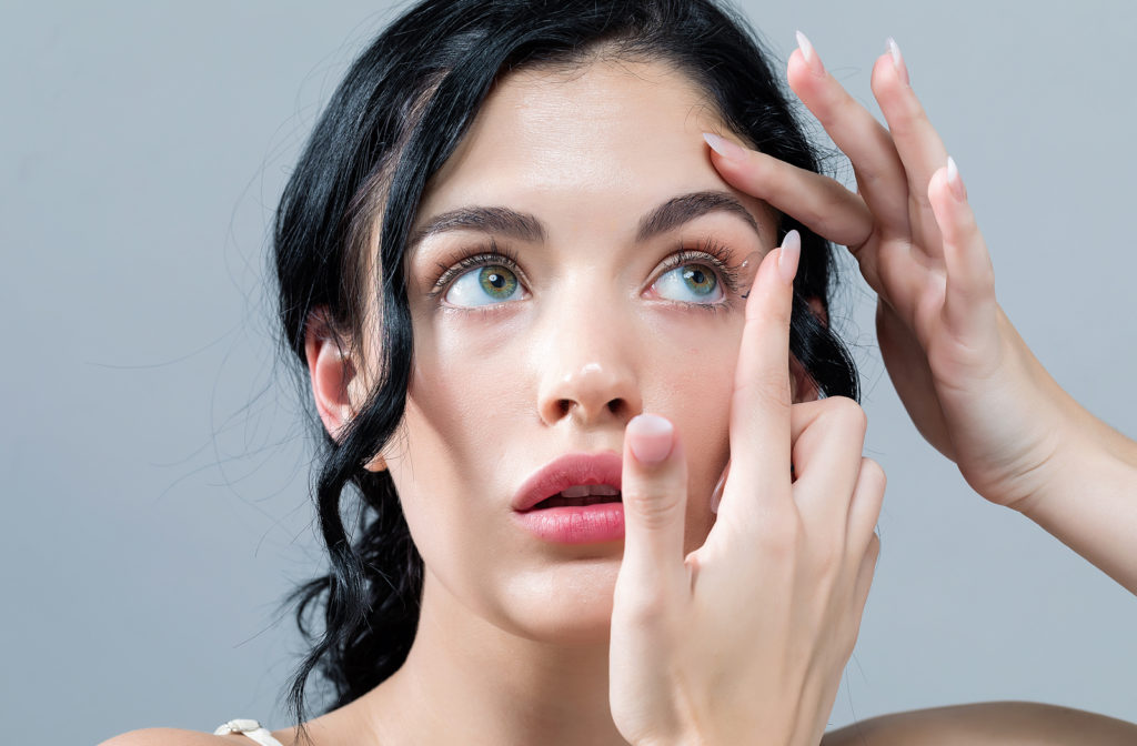 Young woman putting on contact lenses while she looks up on grey background